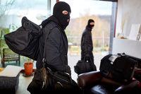 Einbrecher in Haus mit Taschen voller Beute