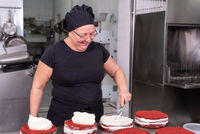Woman pastry chef smiling and working happy, making cakes at the pastry shop.