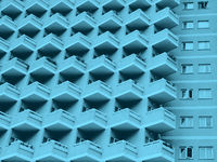 blue toned abstract image of a large residential highrise building with geometric rows of balconies