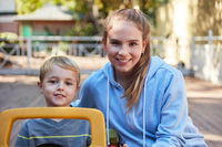 Tagesmutter mit einem Jungen im Tretauto