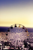 Ferris wheel on background of crowded seaside town