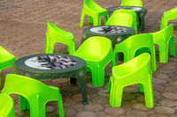 Empty low seat plastic chairs and tables in bright green on the pavement.