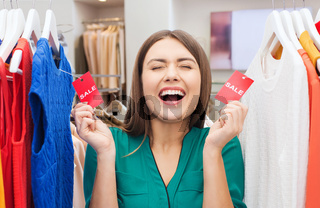 happy woman with sale tags at clothing store