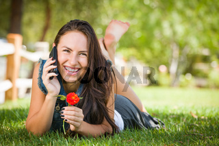 Attractive Happy Mixed Race Young Female Talking on Cell Phone Outside Laying in the Grass