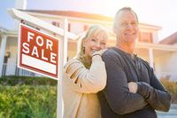 Attractive Middle-aged Couple In Front House and For Sale Real Estate Sign