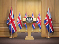 Briefing of prime minister or queen of UK  Great Britain. Podium speaker tribune with flags of Great Britain and UK coat of arms. Politics concept.