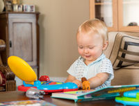 Infant caucasian boy playing with toy computer