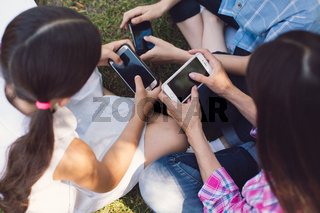 Outdoor portrait of positive kids playing with phones
