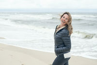 Vivacious laughing woman on a windswept beach