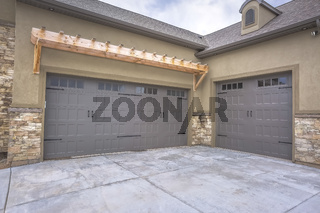Exterior of a home with view of gray double garage doors and stone wall