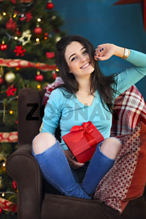 Smiling happy woman with gift box over living room on Christmas tree background. Holidays and people concept