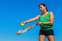 Young colombian woman holds tennis racket and ball