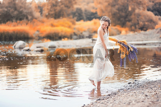 Girl with a bouquet of flowers in autumn