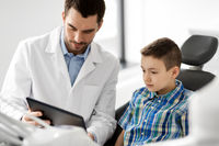 dentist showing tablet pc to kid patient at clinic