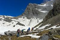 Wanderer durchqueren das Salentse Kar beim Aufstieg zur Rambert Hütte, Wallis, Schweiz