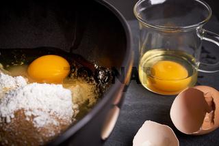 Ruehrschuessel und Glas mit Eiern, Mehl und Zucker