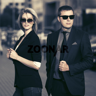 Young fashion business couple walking in city street
