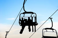 people on chairlift with skis