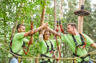 Junge Leute im Hochseilgarten feiern Teamwork
