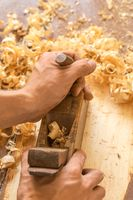 Wooden hand plane. Closeup of woodworker's hands shaving with a plane in a joinery workshop