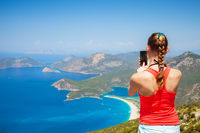 young woman taking a photo of beautiful sea on smartphone