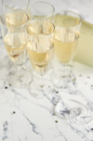 Champagne glasses and bottle placed on white marble background