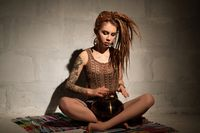 Girl with blonde dreadlocks playing tapidrum view