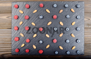 Flat lay view at ripe bilberry raspberry and almond on slate stone tray closeup