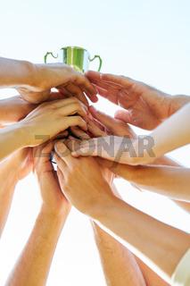 Viele Hände halten den Sieger Pokal