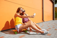 teenage girls with skateboards taking selfie