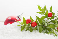 Holly leaves and berries decorations on the snow with a christmas ball on the background