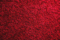 Texture of a dark red carpet. Close-up of gradient light