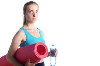 Beautiful caucasian woman holding water bottle while holding yoga mat