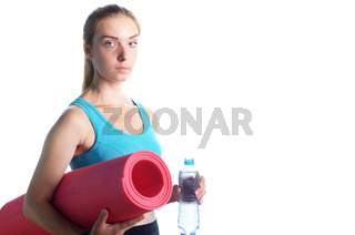 Beautiful caucasian woman holding water bottle while holding yoga mat