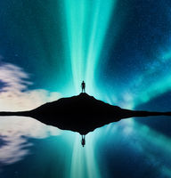 Northern lights and silhouette of standing man in the hill