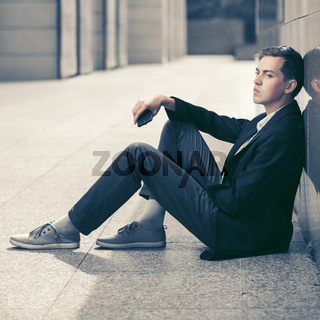 Young fashion business man with a mobile phone sitting at the wall
