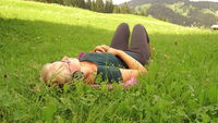 blonde girl listens to music with headphones on a green grass