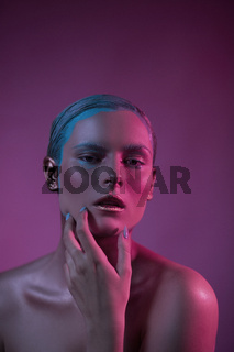 Passionary woman with open lips on pink in creative lighting.