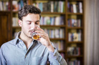 Casual attractive young man drinking water in library