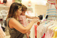 Woman shopping with little baby child girl on hands in clothing shop