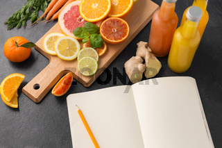 close up of fruits, juices and notebook on table