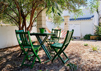 Pretty inner yard with table and chairs under lush green tree and hammock