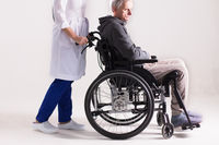 Nurse pushing wheelchair with man in it.