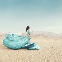 Beautiful young woman in long fluttering dress posing outdoor