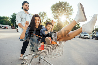 Young dad carries mom and son in a cart on the parking lot