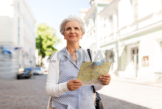 senior woman or tourist with map on city street