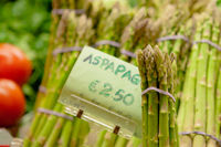 Bunch of green raw asparagus vegetable food on market stall