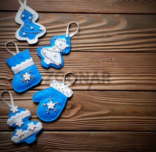 Handmade rustic felt Christmas tree decorations flat laying on wooden table