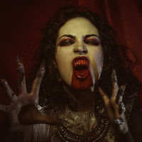 nibble vampire, demonic woman dressed in white lace and silver jewelry. has fangs and thick brown hair