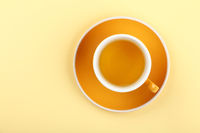 Yellow cup of green oolong tea on saucer